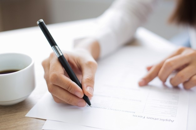 Image shows a person writing on a form.